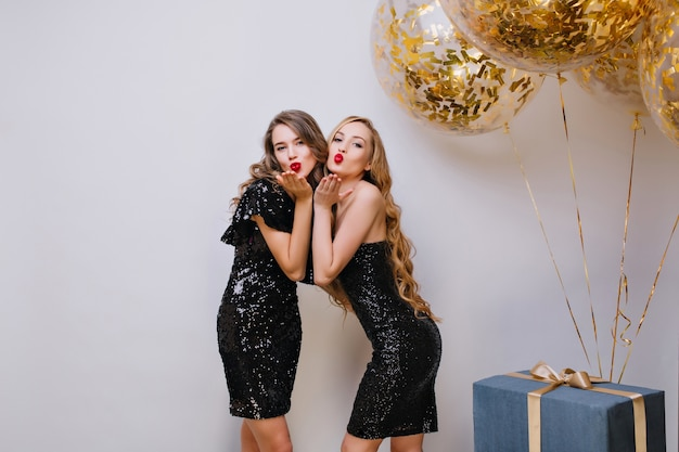Two lovely girls in similar black dresses posing with kissing face expression at birthday party. long-haired european lady standing beside balloons and gifts, sending air kiss.