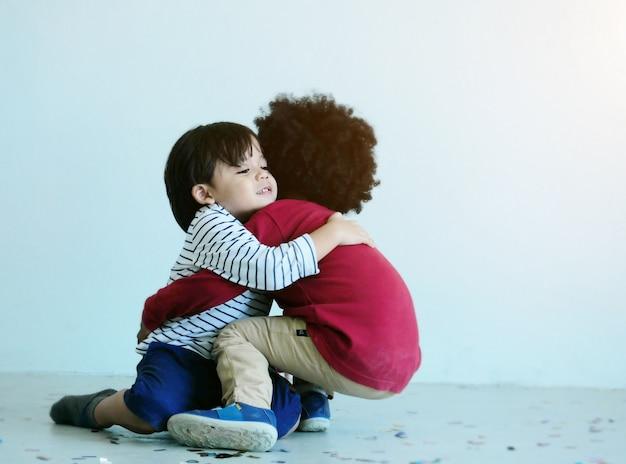 2つの素敵な小さな男の子が学校で一緒に遊んで、ハグします。