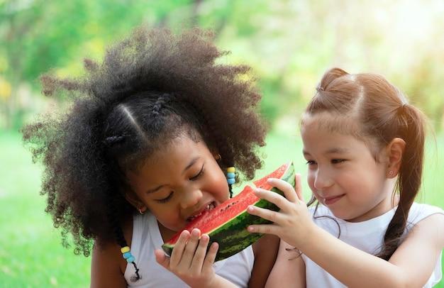 Two lovely little girl eating watermelon in park on summer day.