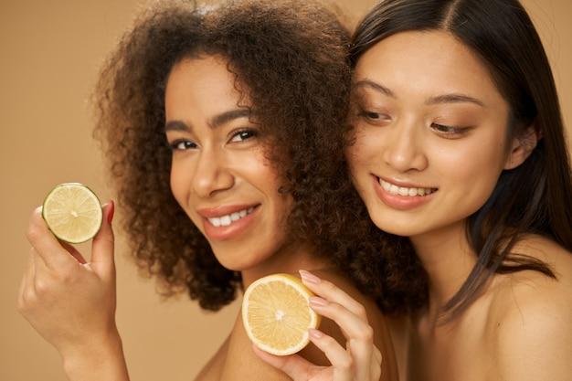 Две очаровательные молодые женщины смешанной расы выглядят взволнованными, держа разрезанные пополам лимон и лайм