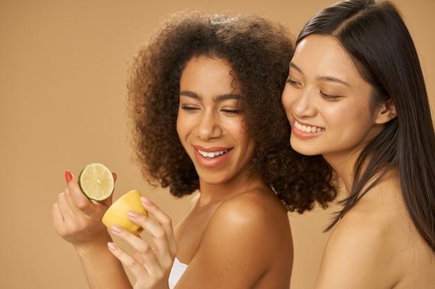 Две милые молодые женщины смешанной расы выглядят счастливыми, держа в руках разрезанный пополам лимон и лайм