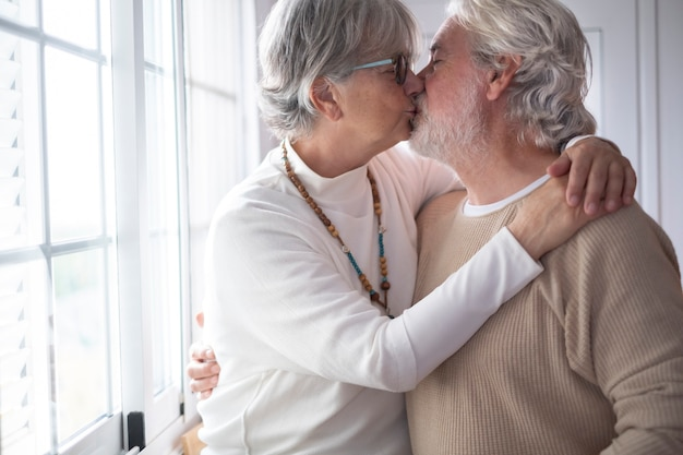 Two lovely old people lovingly kissing in front of the window. concept of love and tenderness
