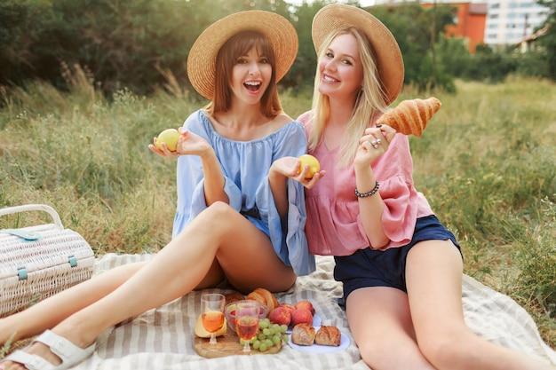 Две милые игривые женщины позируют на лужайке в летнем парке, наслаждаясь вкусной едой, круассанами и вином.