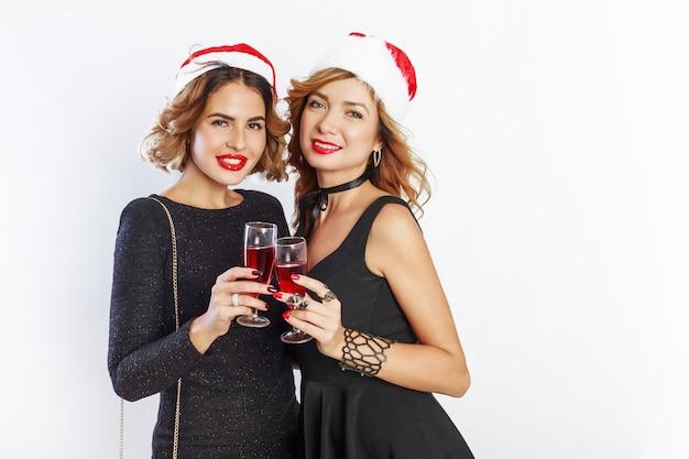 赤いクリスマスのサンタクロースの休日の帽子の2人の素敵なセクシーな女の子が白い背景でポーズをとって、ワイングラスを保持しています。