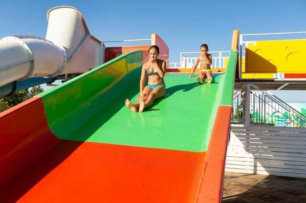 Two lovely sisters descend from a multi-colored bright slide into a pool with clear transparent water