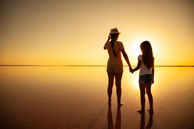 두 사랑스러운 자매는 저녁 불타는 석양에 거울 호수를 따라 걷는다