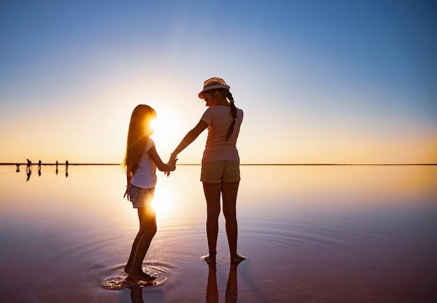 Две милые сестры гуляют по зеркальному озеру в вечернем огненном закате