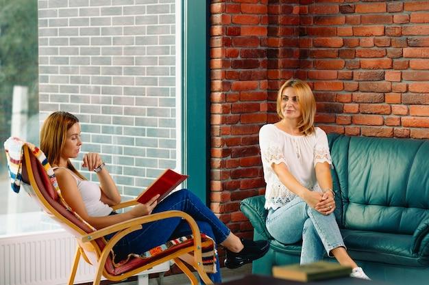 Две милые женщины в уютной обстановке с книгой, в кресле-качалке и болтают с хорошим другом. красивый интерьер с большими окнами.
