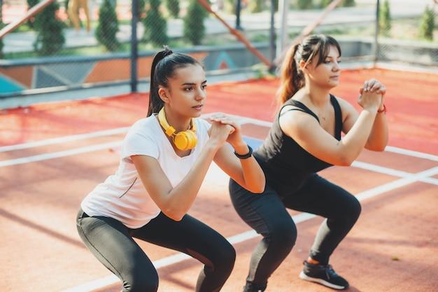 Две милые молодые подруги делают утренние растяжки в спортивном парке для получения хорошей формы. молодая женщина помогает своей подруге похудеть.