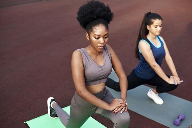 야외에서 훈련하기 전에 요가 매트에 서있는 동안 스트레칭 두 사랑스러운 젊은 여성.
