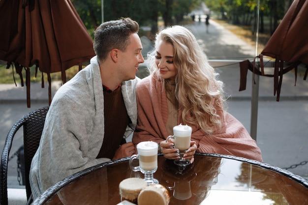 두 연인, 한 남자와 한 여자가 카페의 테이블에. 포옹, 애무, 라떼 마셔. 행복 한 전통 커플, 가족의 행복.