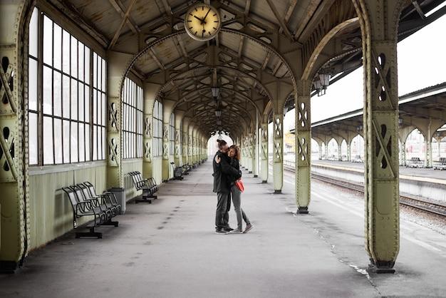 Двое влюбленных обнимаются и целуются на вокзале