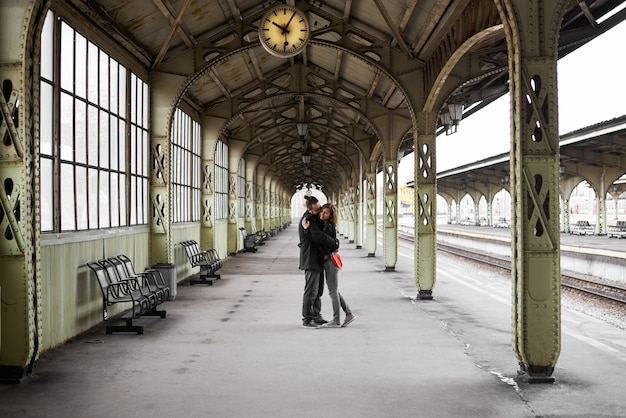 Two lovers hug and kiss on the railway station