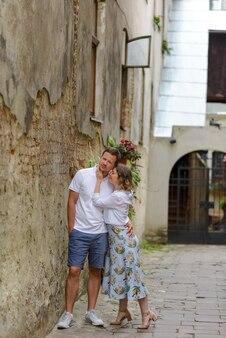 2人の恋人がデート中に旧市街の通りを抱擁します。古いレンガの壁の近くにカップルが立っています。