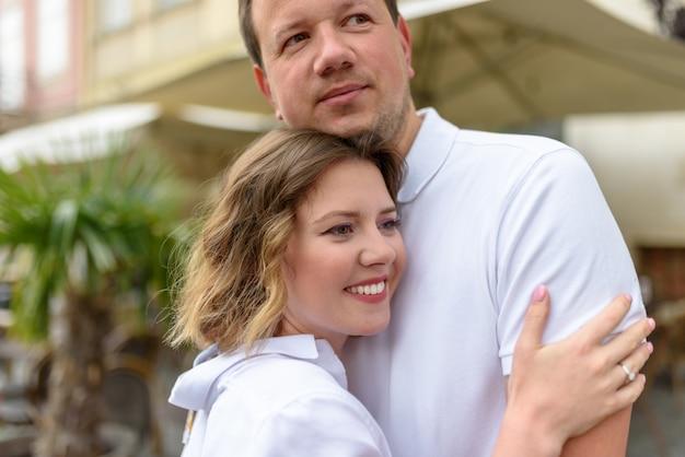 2人の恋人がデート中に旧市街の通りを抱擁します。閉じる