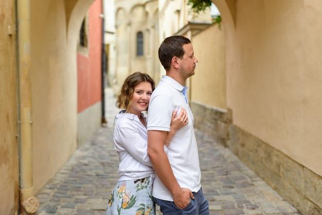 2人の恋人がデート中に旧市街の通りを抱擁します。女の子は男を後ろから抱擁します。