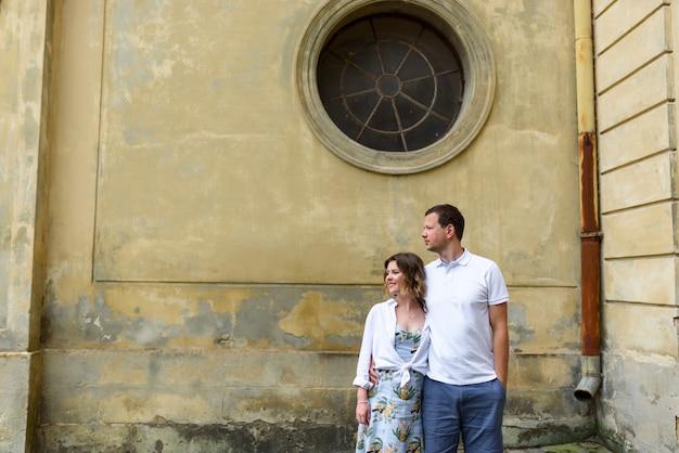 2人の恋人がデート中に旧市街の通りを抱擁します。恋人たちは古い教会に立っています。カップルは目をそらします。