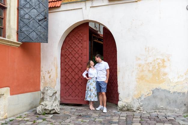 2人の恋人がデート中に旧市街の通りを抱擁します。蒸気は古い赤い門の近くに立っています。