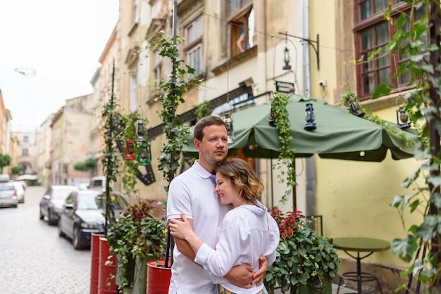 2人の恋人がデート中に旧市街の通りを抱擁します。