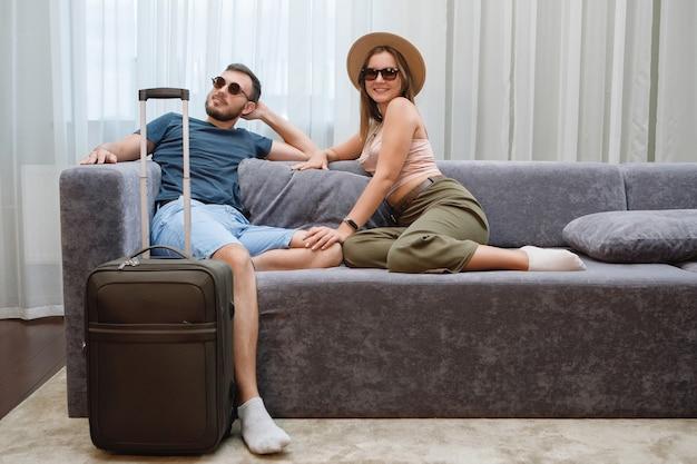 サングラスと帽子をかぶった2人の恋人がソファで楽しんでいます