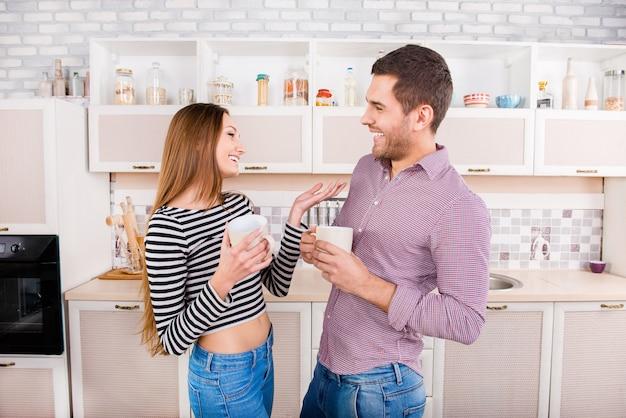 台所で笑ってコーヒーを飲む二人の恋人