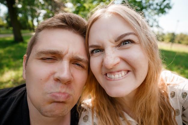 面白い自分撮りを作る2人の恋人、陽気な笑う面白い若者の肖像画。流行に敏感なかわいいカップルが春の公園を歩いています。感情的な表情。美しい晴れた日。