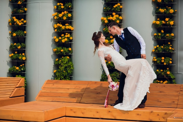 Two lovers sit on a bench, newlyweds crouched to rest in each other's arms during a wedding photo shoot, the bride in a white dress and the groom in a beautiful suit retired in the park.