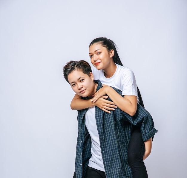 Две любящие женщины носили полосатые рубашки и сидели на спине.