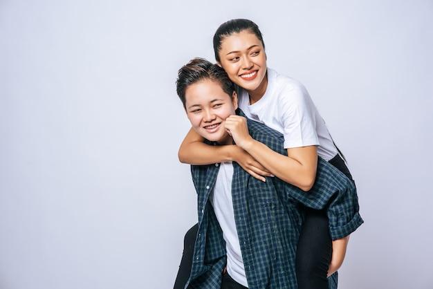 愛情のある2人の女性が縞模様のシャツを着て、背中に乗っていました。