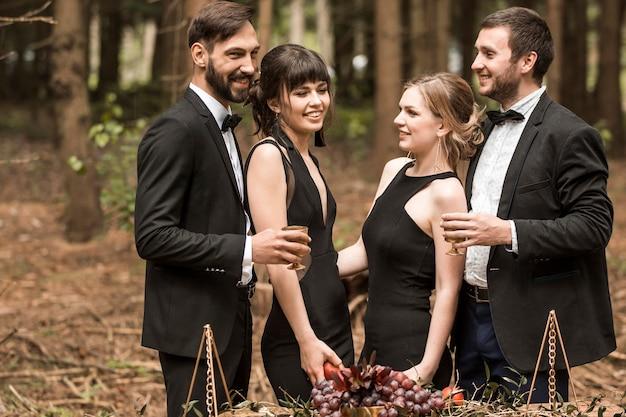 公園でピクニックをしているビジネススーツの2人の愛情のある若いカップル。人とイベント