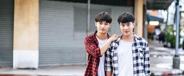 シャツを着て通りに立っている2人の愛する若い男性。