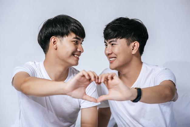 2人の愛する若い男性がお互いを見て、愛のシンボルの手を作ります。