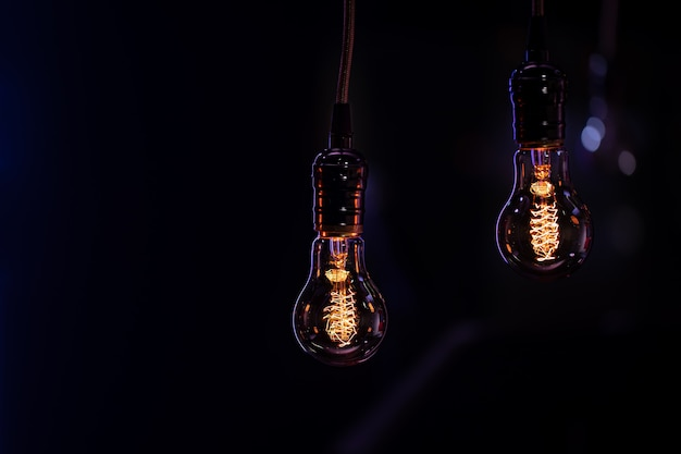Two luminous lamps hang in the dark from the boke. decor and atmosphere concept.