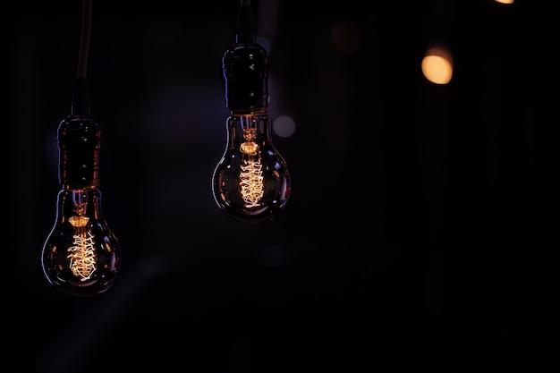2つの発光ランプがボケから暗闇の中でぶら下がっています。装飾と雰囲気のコンセプト。