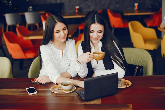 Две роскошные девушки, сидящие в ресторане