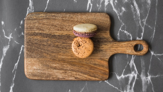 Two macaroons on wooden chopping board over the marble backdrop