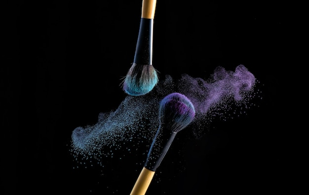 Two make up brushes with powder explosion dust in blue and purple color, close up