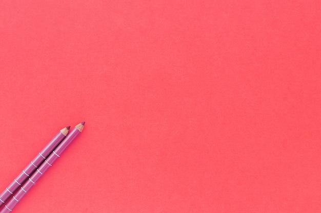 분홍색 배경에 두 메이크업 연필