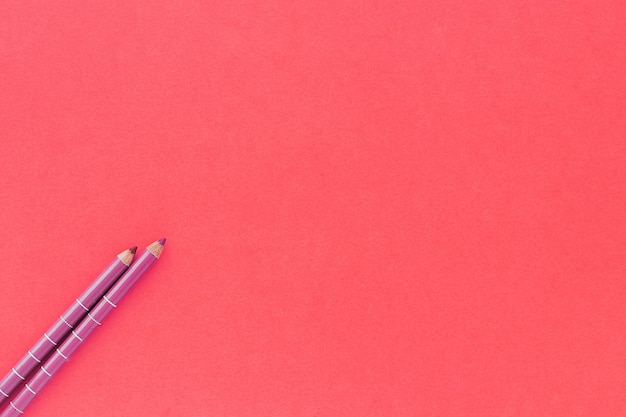 Two make up pencils on pink background