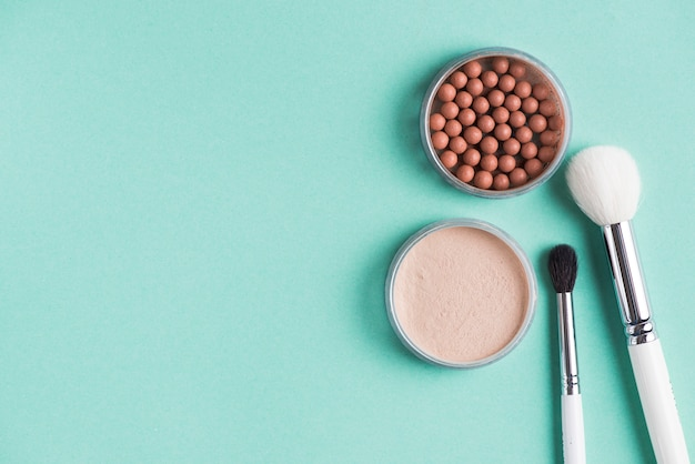 Two makeup brush with compact and bronzed pearls over green backdrop