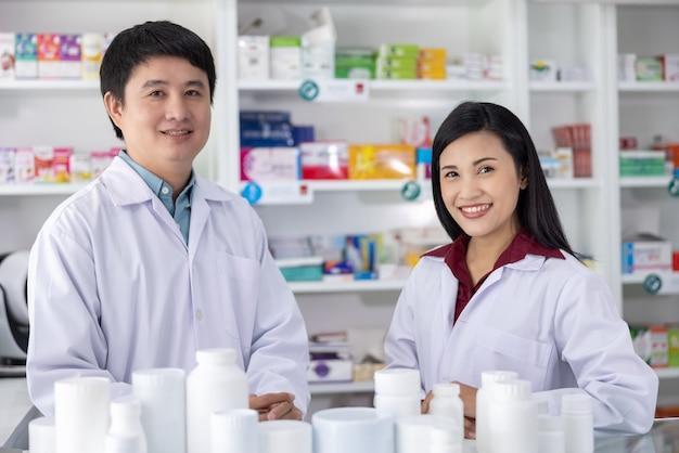 Два мужских и женских фармацевта, улыбаясь, счастливы обслуживать в аптеке таиланда, концепция здравоохранения и бизнеса