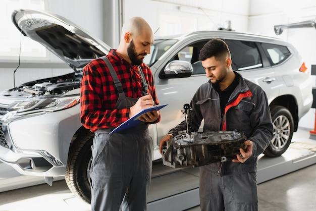 制服の署名車両サービスドキュメントの2つの男性の自動車整備士