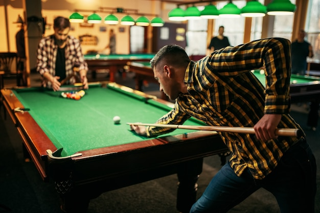 Two male billiard players with cue at the table with colorful balls.