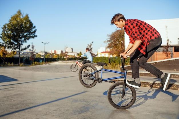 Двое байкеров bmx мужского пола делают трюки в скейтпарке. экстремальный велосипедный спорт, опасные велотренировки, уличная езда, езда на велосипеде в летнем парке