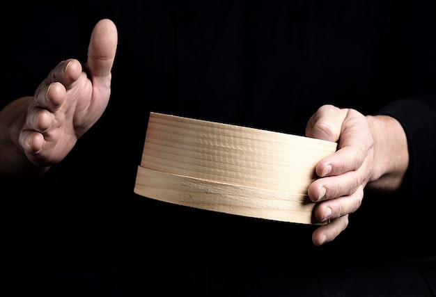 Two male chef hands hold a round wooden sieve