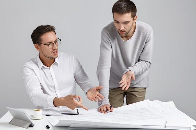 Two male colleagues architects having argument concerning architectural plan, expressing their points of view