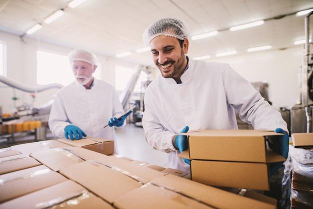 Двое коллег-мужчин в стерильной одежде готовят коробки с продуктами для транспортировки. стоять в светлом помещении или на складе и считать пакет.