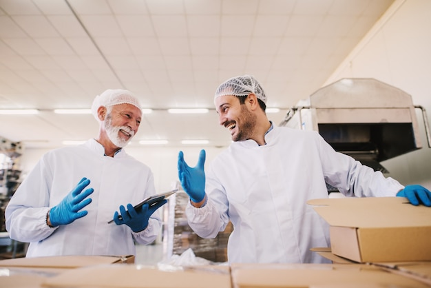 Two male colleagues i sterile clothes preparing boxes with products for transport. standing in bright room or warehouse working together and laughing.