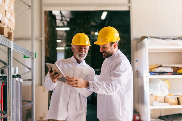 Two male colleagues looking at tablet while standing in warehouse.