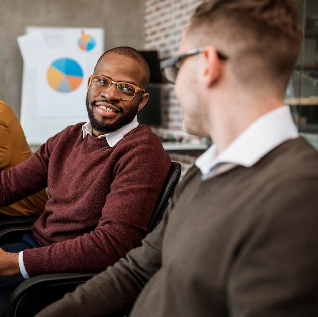 Due colleghi maschi che parlano tra loro durante una riunione